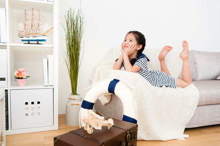 beautiful pretty little kid girl lying down on sofa couch daydreaming and thinking adventure travel plan when she playing in living room.