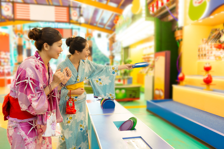attractive young female traveler playing frisbee game when they wearing kimono travel in japan together during summer vacation.