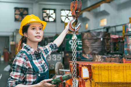 attractive pretty female worker working on milling machine factory and wearing yellow safety hat using chain cranes shipping product. Stock Photo