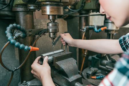 close-up van vrouwelijke fabrieksarbeider werkt aan freesmachine bedrijf en controle fabriek apparaat doet boren componenten werk Stockfoto