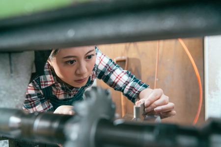 close-up van mooi mooi vrouwenpersoneel die aan het bedrijf van de draaibankmachine en controleapparaat werken om componenten in malenafdeling te verwerken. selectieve focusfoto.