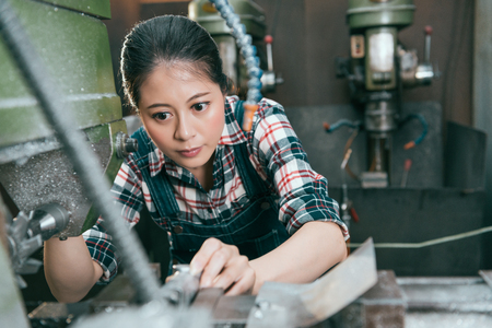 Selective focus on beautiful young female lathe machine factory worker using device doing milling parts work.