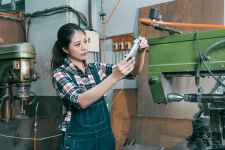 Professional pretty lathe machining factory woman worker confirm components in a workplace when she finished milling processing work.