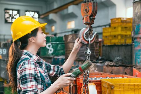 美しい若い製粉機工場の女性労働者調整チェーンクレーン機械加工出荷旋盤完成品を準備します。 写真素材