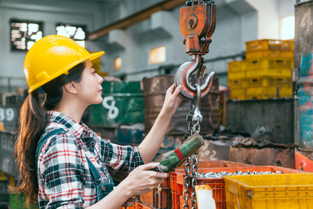 Beautiful young milling machine factory female worker adjusting chain cranes machining preparing shipping lathe finished products. Archivio Fotografico