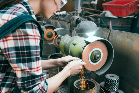 young professional female milling machine company employee wearing safety glasses working on grinding wheel and processing components with sparks in workshop.