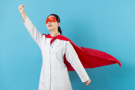 cheerful pretty female clinic doctor with superhero clothing and making go posture preparing to fight all disease isolated on blue background. Archivio Fotografico