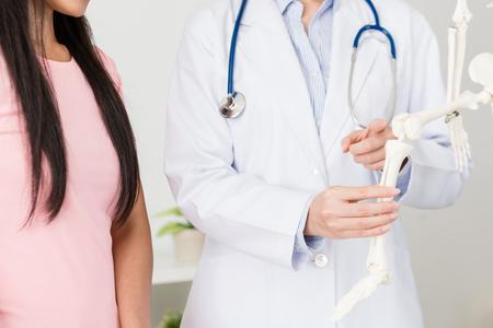 żeński lekarz szpitalny przy użyciu modelu szkieletu ilustrującego plan operacji i wskazującego kolano dla pacjenta omawiającego leczenie.