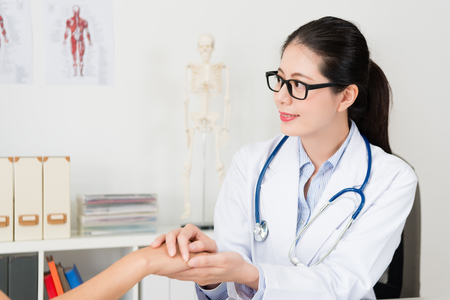 attractive pretty woman doctor touching patient hand and care sick problem to encourage treatment.