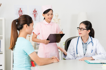 pretty beauty female doctor explaining sickness status for patient and nurse writing medical record on clipboard in clinic. Stock Photo