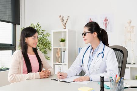 lächelnder Jugendlicher des jungen Mädchens, der Grippe krank erhält und Berufsdoktor besucht, um krankes Problem im Klinikbüro zu beraten. Standard-Bild
