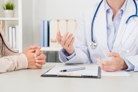Nahaufnahme der Ärztin erklären Krankheitsbehandlungslösung für Patienten in der Klinik. Foto des vorgewählten Fokus.