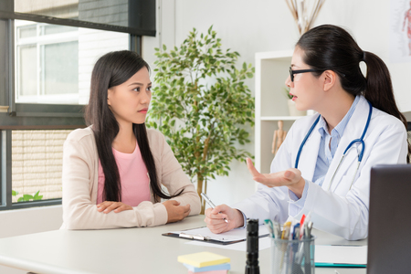 professional young female doctor explaining disease severity for patient and giving good treatment solution suggestion. Stock Photo