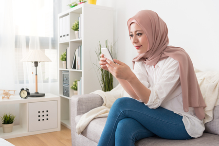 smiling attractive muslim lady sitting on sofa couch and using mobile smartphone browsing online social software information.