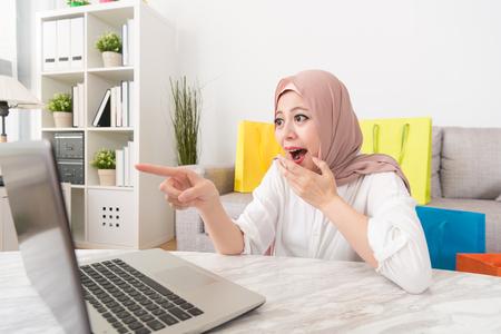 彼女はスーパーセールを持っているオンラインショッピングサイトを見つけたときにショックを受けたモバイルコンピュータの画面を指し示す陽気