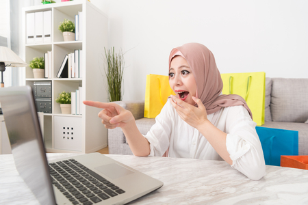 cheerful pretty muslim woman pointing mobile computer screen feeling shocked when she finding online shopping website having super sale. 스톡 콘텐츠