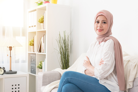 confident young muslim woman sitting on sofa couch at home during sunny day and hands crossed put on chest looking at camera smiling.