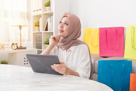 Mujer musulmana bastante atractiva mirando aire soñando despierto pensando cuando ella usa la computadora móvil pad compras en línea en casa.