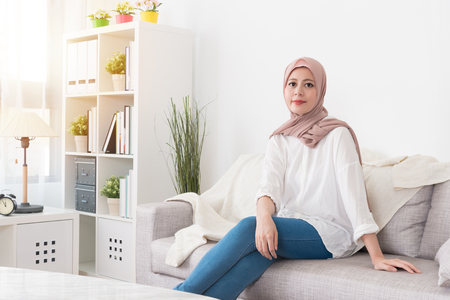 pretty elegant muslim woman sitting on sofa couch relaxing in living room at home and looking at camera smiling during sunny day. Stock Photo