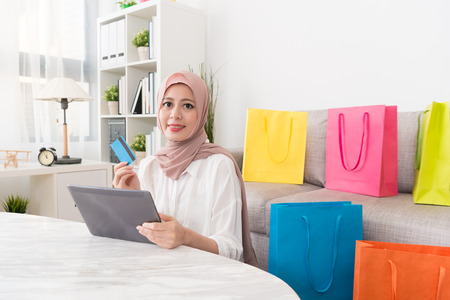 happy elegant muslim woman using mobile pad computer online shopping at home and paying through personal credit card e-commerce system.