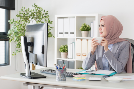 smiling beautiful muslim business woman drinking hot coffee sitting in workspace and looking at window outside thinking work plan.