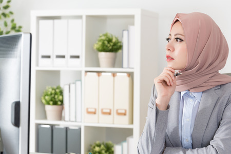 closeup photo of pretty beauty muslim business woman looking at outside daydreaming and thinking company work plan for future.