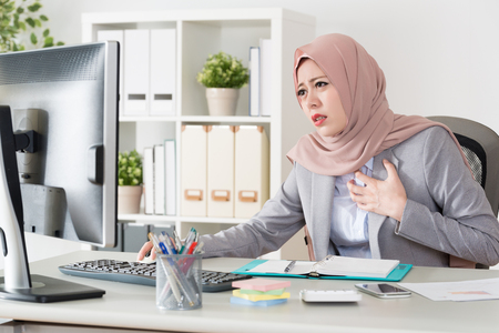 attractive young female muslim office worker having palpitation problem and feeling painful suffering when she working in office. Imagens