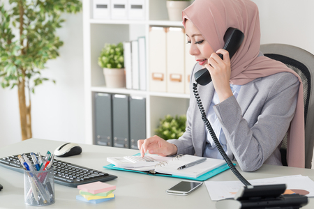 elegant beauty muslim business woman using calculator counting budget when she talking with customer through office telephone.