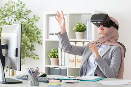 elegant attractive female muslim office worker wearing VR technology glasses sitting in workplace and using hands touching 3D simulation to organize work plan. Stok Fotoğraf