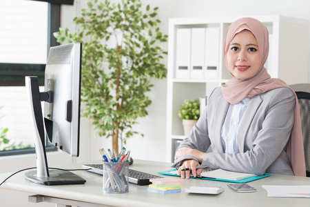 attractive elegant female muslim business office worker working with computer and face to camera smiling. Archivio Fotografico