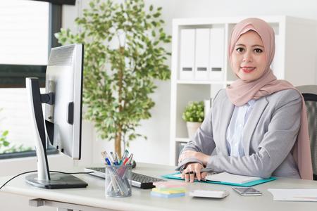 Attraktive elegante weibliche muslimische Büroangestellte arbeiten mit Computer und Gesicht zu denken lächelnd