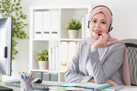 confident pretty female muslim office operator working in company service center and face to camera smiling.