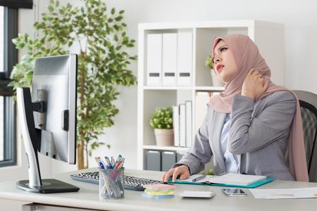オフィスに座っている若いかわいいイスラム教徒のビジネスウーマンは、長時間働いて疲れを感じ、手マッサージを使用して首が痛みます。