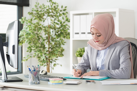 attractive pretty muslim woman manager using pen writing personal schedule on notebook when she working in company office.