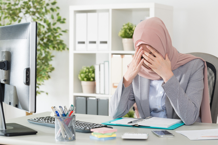 professional young female muslim worker having problem about company cooperation case feeling sad and sitting in office thinking solution.