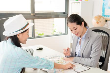 mooie elegante vrouwelijke reiziger bezoekend reisbureau bedrijf en wijzende kaart om professionele kantoormedewerker reisschema te vragen.