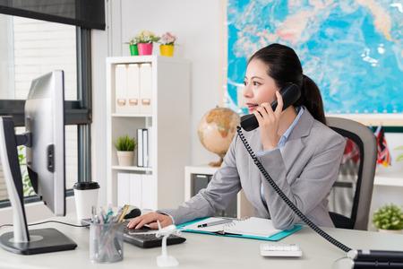 schöner eleganter weiblicher Büroangestellter, der den Computer sucht Flugticketstatus betrachtet, wenn sie das Telefon verwendet, das mit dem Kunden spricht, der Reiseplan bespricht.