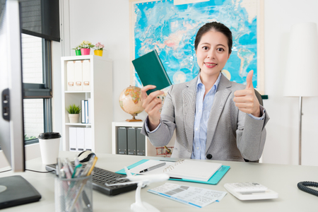 smiling pretty woman manager showing thumb up gesture with passport looking at camera when she sitting in travel agent office. Reklamní fotografie