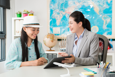 beautiful pretty female business worker using mobile digital tablet showing travel itinerary plan for smiling happy traveler. Stock Photo