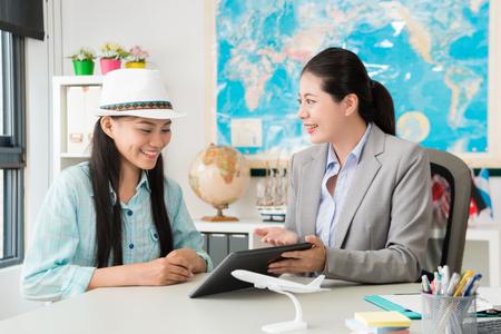 mooie mooie vrouwelijke zakelijke werknemer met behulp van mobiele digitale tablet met reisplan voor lachende gelukkige reiziger. Stockfoto
