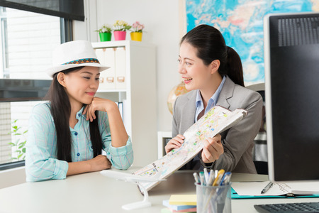 smiling professional business worker woman holding map introducing travel itinerary for young female customer. Stock Photo