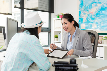 cheerful young female travel agent company business manager using mobile digital tablet introducing special journey itinerary for traveler girl. Stock Photo