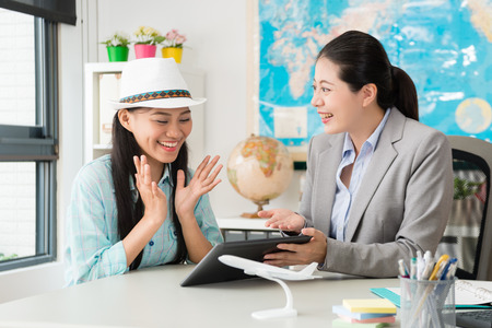 cheerful elegant female customer feeling happy when travel agent company manager woman using mobile pad computer showing special price for her.
