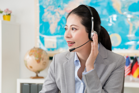 happy friendly female travel agent company operator wearing headset microphone talking with customer discussing journey schedule plan.