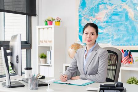 Agente de viajes femenino joven y confiado que brinda a todos los viajeros el mejor servicio y ayuda a planificar el horario.