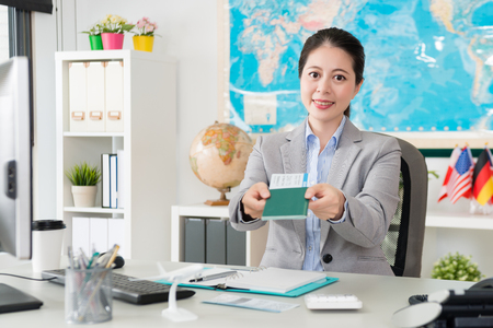 beautiful pretty female travel agent company office worker holding passport with airline ticket and face to camera giving for client.