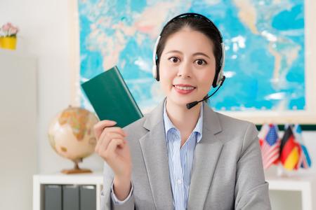 pretty elegant travel agent company female operator looking at camera showing passport.