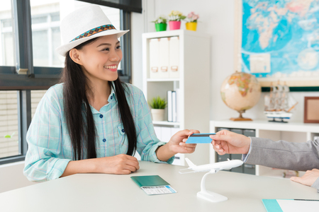 smiling pretty woman traveler giving credit card for travel agent when she booking itinerary.