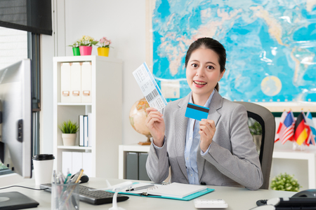 happy confident female business worker working on travel agent company and showing using credit card buying airline ticket concept. Banco de Imagens