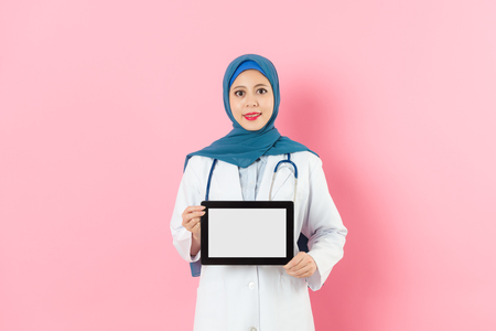 smiling professional muslim female doctor standing in pink background and holding mobile digital tablet face to camera showing blank screen. Stok Fotoğraf